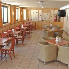 Gemütliches Café mit Blick auf Spielzimmer im JUFA Hotel Bad Aussee. Der Ort für erholsamen Familienurlaub und einen unvergesslichen Winter- und Wanderurlaub.