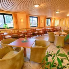 Gemütliches Café mit Fensterfront und Blick auf Spielzimmer im JUFA Hotel Bad Aussee. Der Ort für erholsamen Familienurlaub und einen unvergesslichen Winter- und Wanderurlaub.