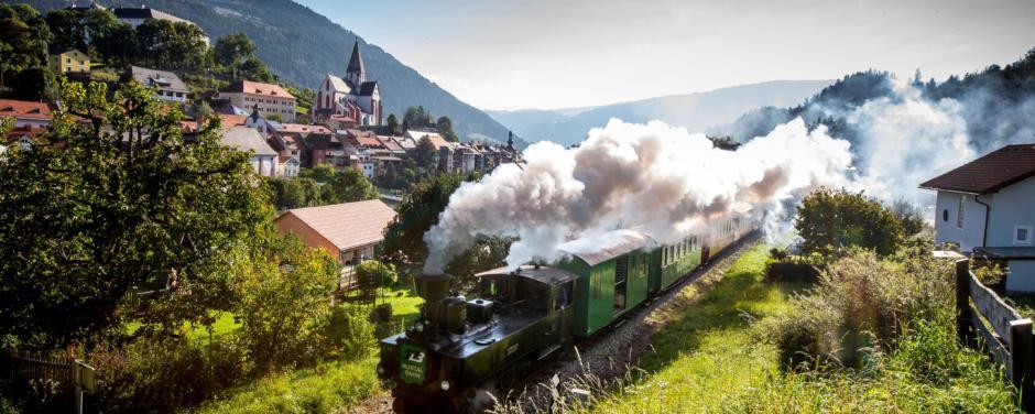 Dampfbummelzug Murtalbahn fährt in Murtal-Spielberg durch die Landschaft in der Nähe von JUFA Hotels. Der Ort für erholsamen Familienurlaub und einen unvergesslichen Winter- und Wanderurlaub.