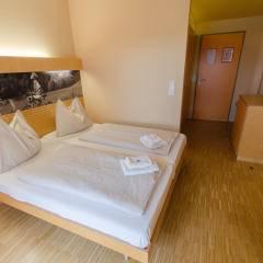 Doppelbett in einem Doppelzimmer mit Blick auf die Eingangstüre und Garderobe im JUFA Hotel Deutschlandsberg Sport-Resort. Der Ort für erfolgreiches Training in ungezwungener Atmosphäre für Vereine und Teams.