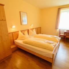 Doppelbett im Doppelzimmer im JUFA Hotel Grundlsee. Der Ort für tollen Sommerurlaub an schönen Seen für die ganze Familie.