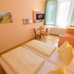 Doppelbett im Doppelzimmer im JUFA Hotel Kaprun mit TV. Der Ort für erholsamen Familienurlaub und einen unvergesslichen Winter- und Wanderurlaub.