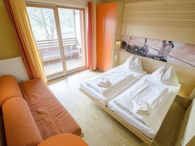 Doppelbett im Doppelzimmer im JUFA Hotel Leibnitz Sport-Resort mit Sofa. Der Ort für erfolgreiches Training in ungezwungener Atmosphäre für Vereine und Teams.