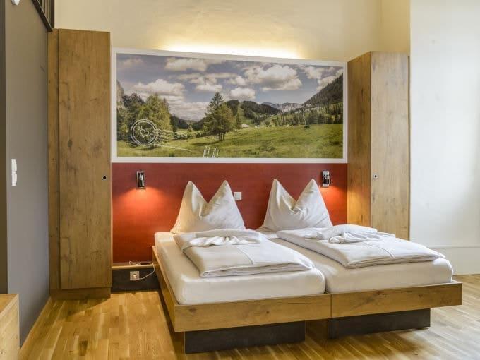 Doppelbett im Doppelzimmer im JUFA Hotel Pyhrn-Priel mit Wandbild. Der Ort für erfolgreiche und kreative Seminare in abwechslungsreichen Regionen.