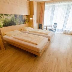 Doppelbett im Doppelzimmer im JUFA Natur-Hotel Bruck mit Sofa. Der Ort für erfolgreiche und kreative Seminare in abwechslungsreichen Regionen.