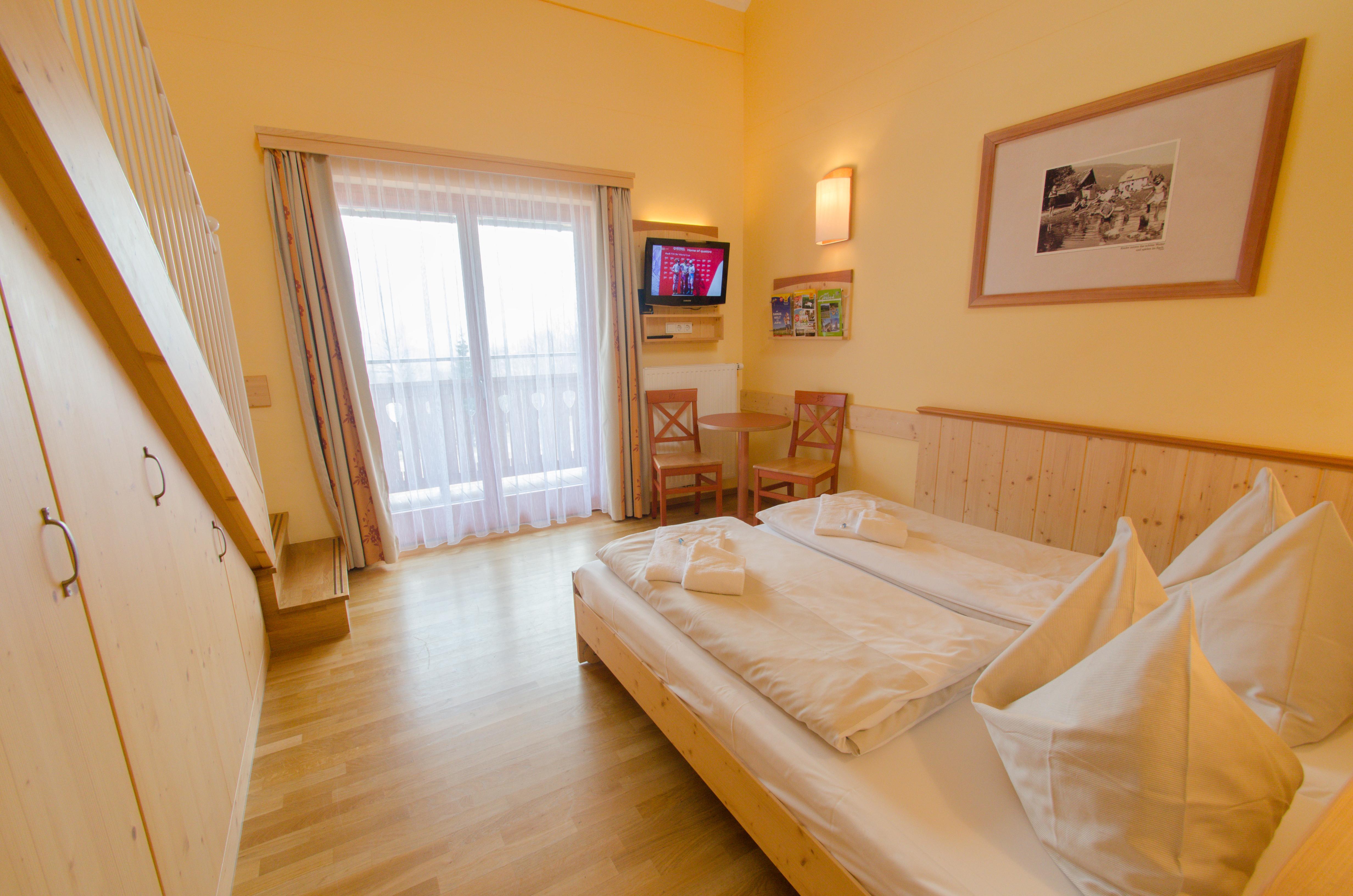 Doppelbett im Galeriezimmer large im JUFA Hotel Gitschtal Landerlebnis mit TV. Der Ort für kinderfreundlichen und erlebnisreichen Urlaub für die ganze Familie.