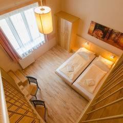 Doppelbett im Galeriezimmer large im JUFA Natur-Hotel Bruck mit Galerieblick. Der Ort für erfolgreiche und kreative Seminare in abwechslungsreichen Regionen.