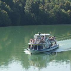 Schiff fährt auf der Drau in Südkärnten im Sommer in der Nähe von JUFA Hotels. Der Ort für erholsamen Familienurlaub und einen unvergesslichen Winter- und Wanderurlaub.