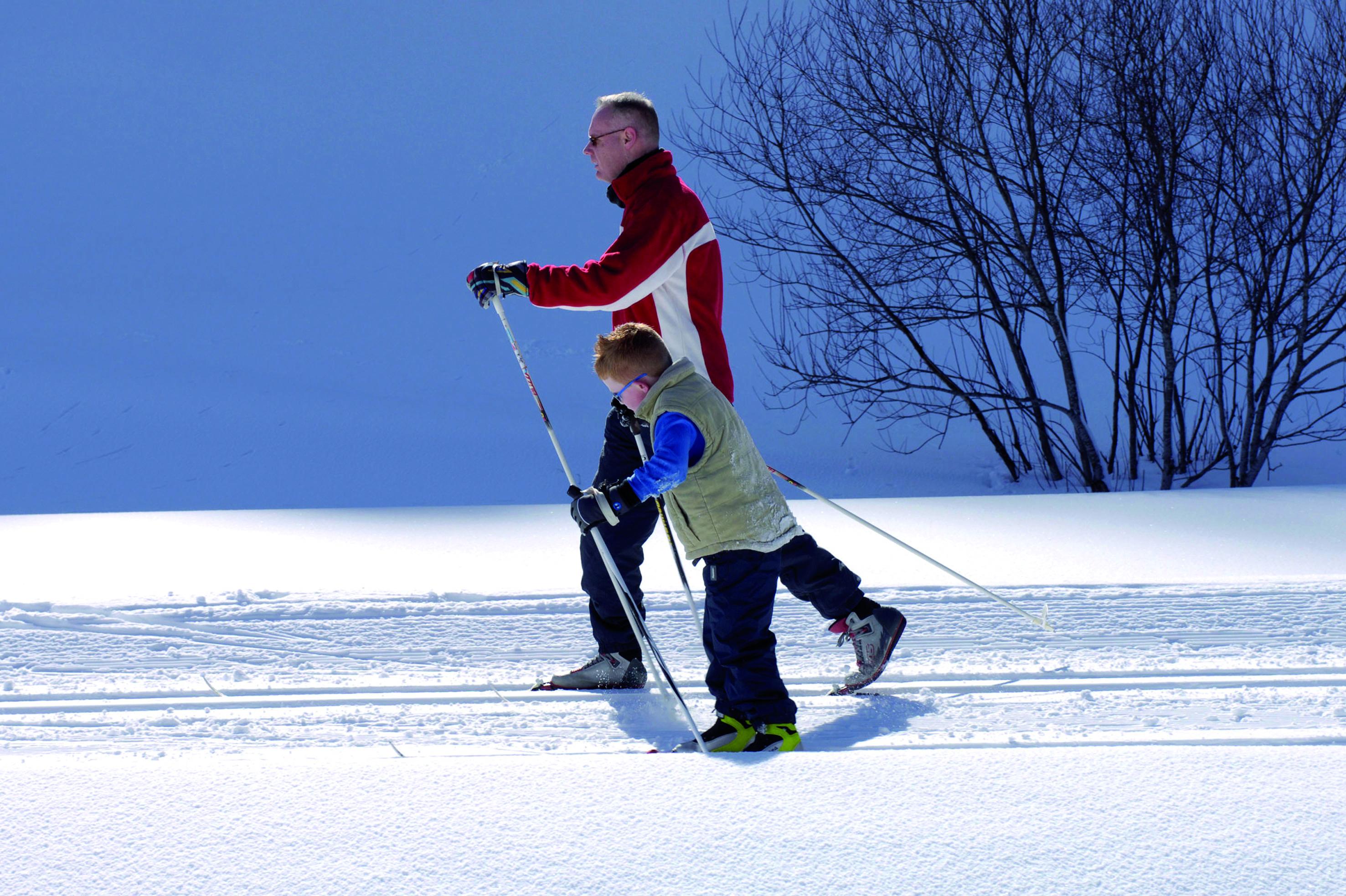 Vater und Sohn beim Langlaufen in der Eisenerzer Ramsau in der Nähe von JUFA Hotels. Der Ort für erholsamen Familienurlaub und einen unvergesslichen Winterurlaub.
