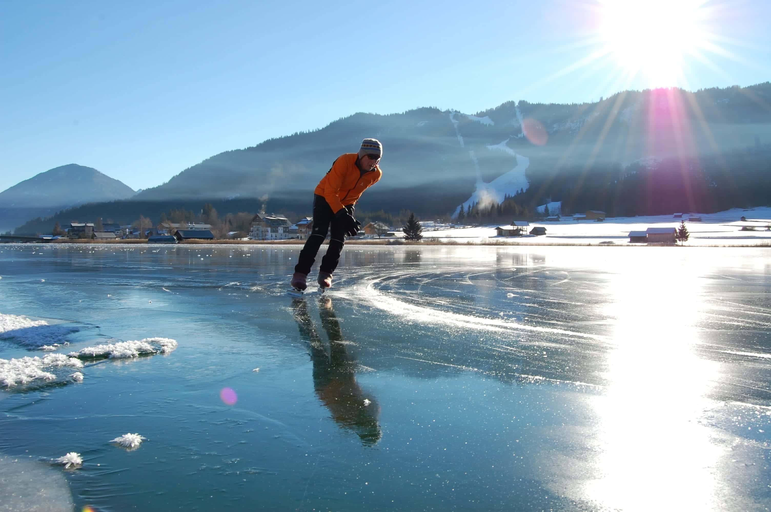Sie sehen einen Mann am Weissensee im Winter eislaufen. JUFA Hotels bieten erholsamen Familienurlaub und einen unvergesslichen Winter- und Wanderurlaub