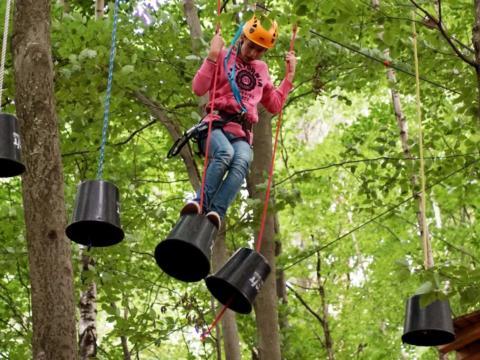 Mädchen klettert im Hochseilgarten im Erlebnispark Geier. JUFA Hotels bietet kinderfreundlichen und erlebnisreichen Urlaub für die ganze Familie.