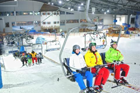 Erwachsene und Kinder auf Sessellift in der Skihalle Neuss in Nordrhein-Westfalen.  JUFA Hotels bietet kinderfreundlichen und erlebnisreichen Urlaub für die ganze Familie.