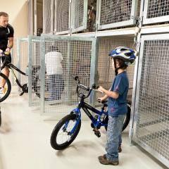 Familie holt Fahrräder aus dem Fahrradabstellraum im JUFA Hotel Deutschlandsberg - Sport-Resort. Der Ort für erfolgreiches Training in ungezwungener Atmosphäre für Vereine und Teams.