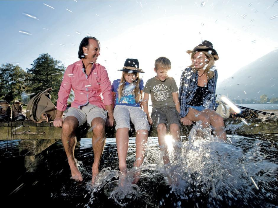 Familie lässt nach einer Wanderung die Beine ins Wasser baumeln am Ossiacher See in der Nähe von JUFA Hotels. Der Ort für erholsamen Familienurlaub und einen unvergesslichen Winter- und Wanderurlaub.
