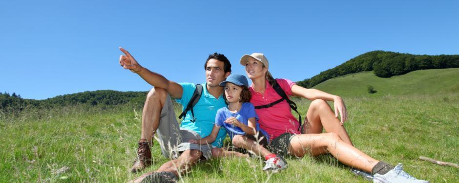 Familie sitzt in der Wiese und macht Wanderpause. JUFA Hotels bietet erholsamen Familienurlaub und einen unvergesslichen Winter- und Wanderurlaub.