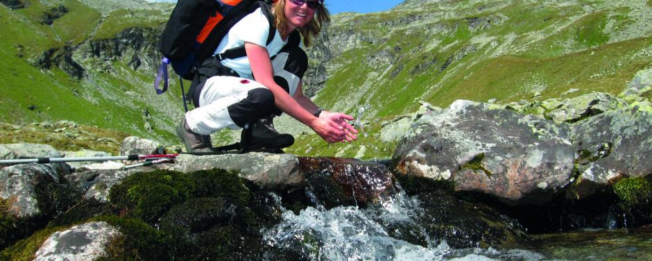 Frau erfrischt sich an einem Gebirgsbach in den Bergen in der Steiermark in der Nähe von JUFA Hotels. Der Ort für erholsamen Familienurlaub und einen unvergesslichen Winter- und Wanderurlaub.
