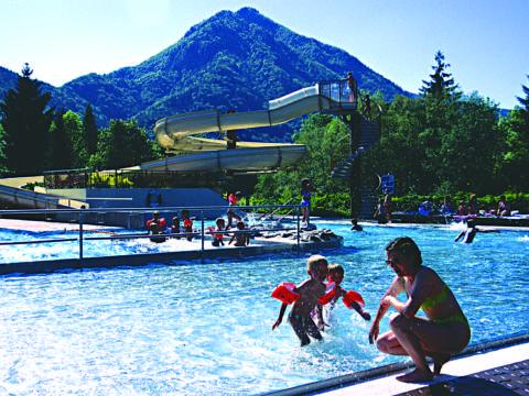 Sie sehen das Freibad in Grünau mit Kindern und einer Wasserrutsche. JUFA Hotels bietet kinderfreundlichen und erlebnisreichen Urlaub für die ganze Familie.