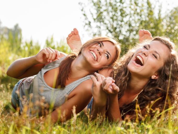 Freundinnen liegen auf einer Wiese im Sommer und lachen ausgelassen im JUFA Urlaub. Der Ort für erholsamen Familienurlaub und einen unvergesslichen Winter- und Wanderurlaub.