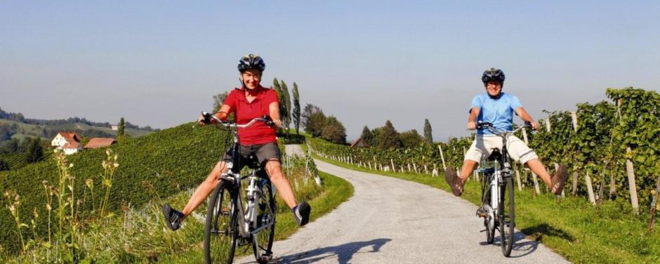 Paar fährt gemütlich mit dem Rad durch die Südoststeiermark, vorbei an Weinfeldern in der Nähe von JUFA Hotels. Der Ort für erholsamen Familienurlaub und einen unvergesslichen Winter- und Wanderurlaub.