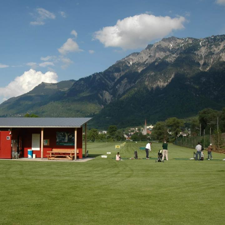 Golfer am Abschlagplatz auf der Golf Driving Range in Schaan. JUFA Hotels bietet Ihnen den Ort für erlebnisreichen Natururlaub für die ganze Familie.
