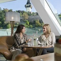Sie sehen Zwei Frauen sitzen im Café auf der Murinsel in Graz mit Blick auf den Uhrturm. JUFA Hotels bietet erlebnisreichen Städtetrip für die ganze Familie und den idealen Platz für Ihr Seminar.