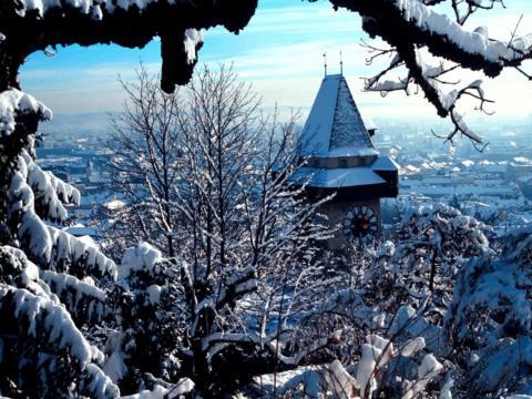 Schneebedeckter Grazer Uhrturm auf Schloßberg mit Stadtblick im Winter. JUFA Hotels bietet erlebnisreichen Städtetrip für die ganze Familie und den idealen Platz für Ihr Seminar.