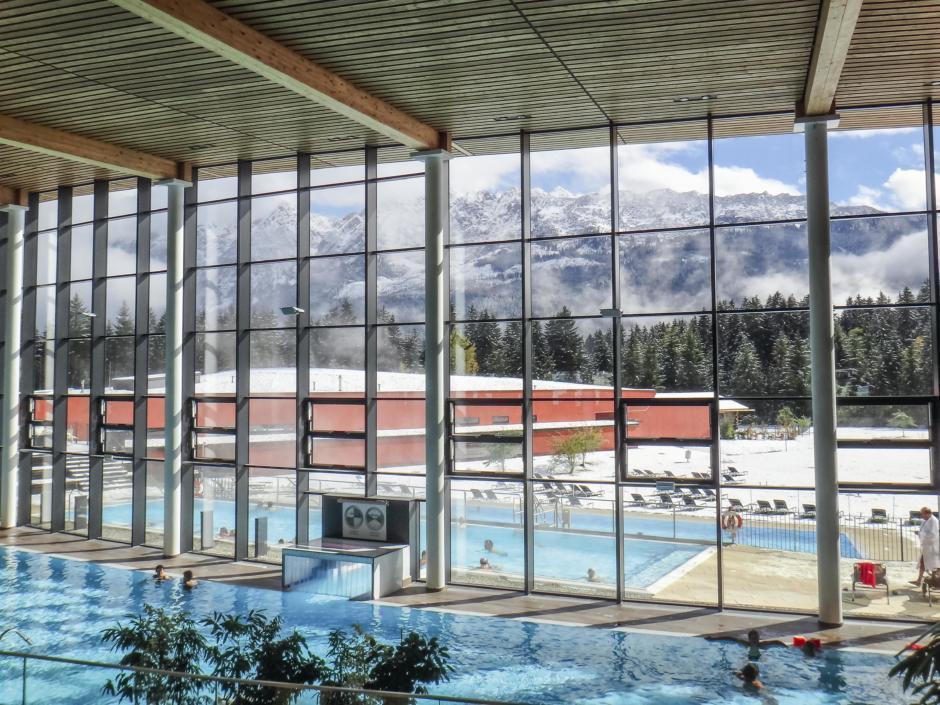 Innenansicht der Therme Grimming mit Fensterfront und Panoramablick in die Winterlandschaft in der Nähe von JUFA Hotels. Der Ort für erholsamen Familienurlaub und einen unvergesslichen Winter- und Wanderurlaub.