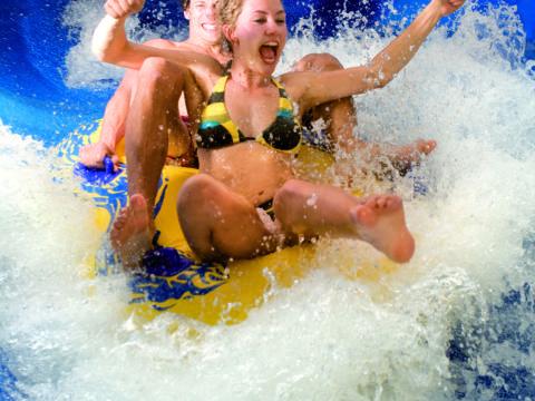 Paar im Schwimmreifen auf der Wasserrutsche in der H2O-Therme in der Nähe von JUFA Hotels. Der Ort für erholsamen Familienurlaub und einen unvergesslichen Winter- und Wanderurlaub.