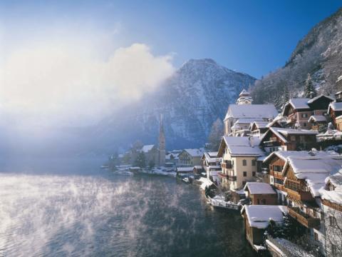 Hallstatt im Salzkammergut mit schneebedeckten Hausdächern im Winter in der Nähe von JUFA Hotels. Der Ort für erholsamen Familienurlaub und einen unvergesslichen Winter- und Wanderurlaub.
