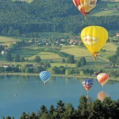 Bunte Heißluftballons über dem Stubenbergsee in der Nähe vom JUFA Hotel Stubenbergsee. Der Ort für tollen Sommerurlaub an schönen Seen für die ganze Familie.