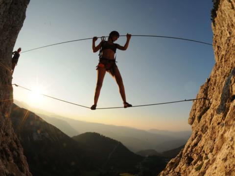 Erwachsene klettert über Schlucht am Heli-Kraft Klettersteig im Hochkar. JUFA Hotels bietet Ihnen den Ort für erlebnisreichen Natururlaub für die ganze Familie.