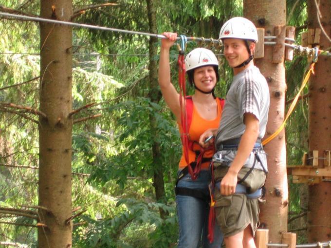 Zwei Erwachsene klettern im Hochseilgarten Bujaka Skyline am Erlaufsee in der Nähe vom JUFA Hotel Veitsch. Der Ort für erholsamen Familienurlaub und einen unvergesslichen Winter- und Wanderurlaub.