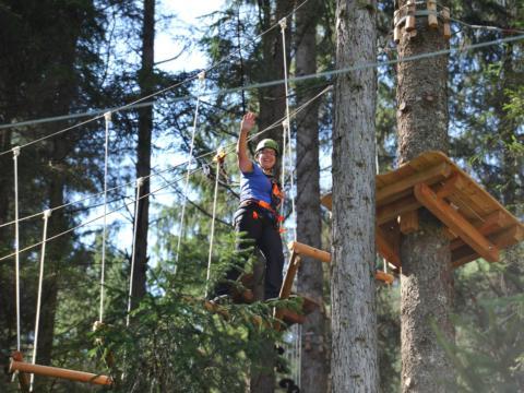 Frau im Hochseilgarten Oberwölz in der Steiermark. JUFA Hotels bieten erholsamen Familienurlaub und einen unvergesslichen Winter- und Wanderurlaub.