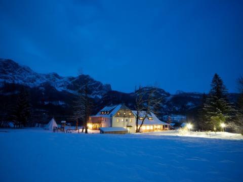 Aussenansicht bei winterlicher Abenstimmung vom JUFA Hotel Grundlsee. Der Ort für erholsamen Familienurlaub und einen unvergesslichen Winterurlaub.