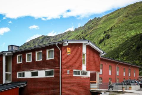 Aussenansicht vom JUFA Hotel Planneralm - Alpin-Resort mit Parkplatz im Sommer. JUFA Hotels bieten erholsamen Familienurlaub und einen unvergesslichen Winter- und Wanderurlaub.