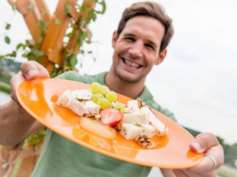 Mann mit Käseplatte in der Käsemacherwelt in Vitis im Waldviertel. JUFA Hotels bieten erholsamen Familienurlaub und einen unvergesslichen Winter- und Wanderurlaub.