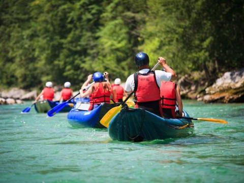 Erwachsene beim Paddeln bei einer Kanutour im Sommer. JUFA Hotels bietet starkes und kreatives Teambuildung in abwechslungsreichen Regionen.