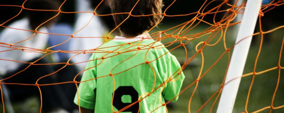 Kind mit Fußballtrikot im Fußballtor. JUFA Hotels bietet Ihnen den Ort für erfolgreiches Training in ungezwungener Atmosphäre für Vereine und Teams.