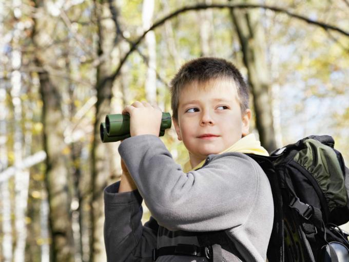 Junge mit Fernglas auf Entdeckungstour in der Natur. JUFA Hotels bietet Ihnen den Ort für erlebnisreichen Natururlaub für die ganze Familie.