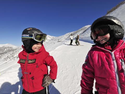 Kinder lachend beim Skifahren in Malbun. JUFA Hotels bietet erholsamen Familienurlaub und einen unvergesslichen Winterurlaub.