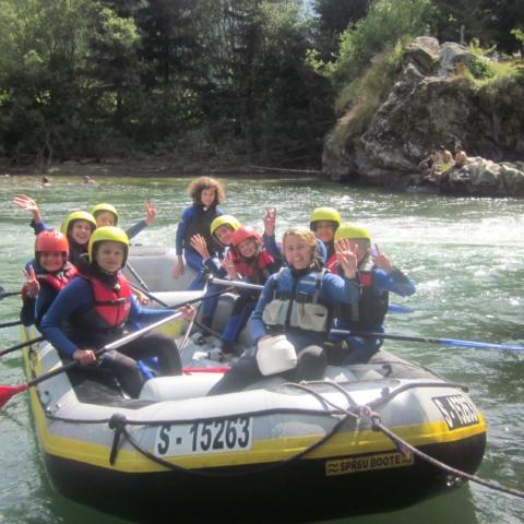 Glückliche Kinder im Rafting-Schlauchboot mitten im Abenteuer. JUFA Hotels bietet erlebnisreiche Feriencamps in den Bereichen Sport, Gesundheit, Bildung und Sprachen.