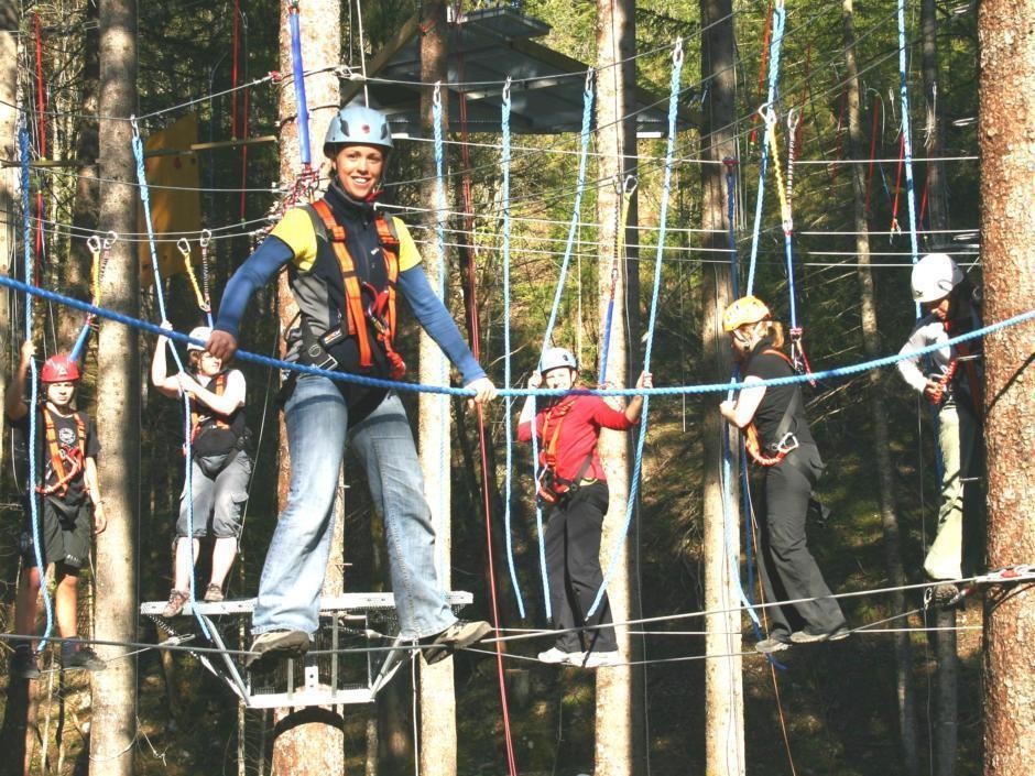 Sie sehen den Hochseil-Kletterpark  Omunduntn mit Kindern. JUFA Hotels bietet erlebnisreiche und kreative Schulprojektwochen in abwechslungsreichen Regionen.