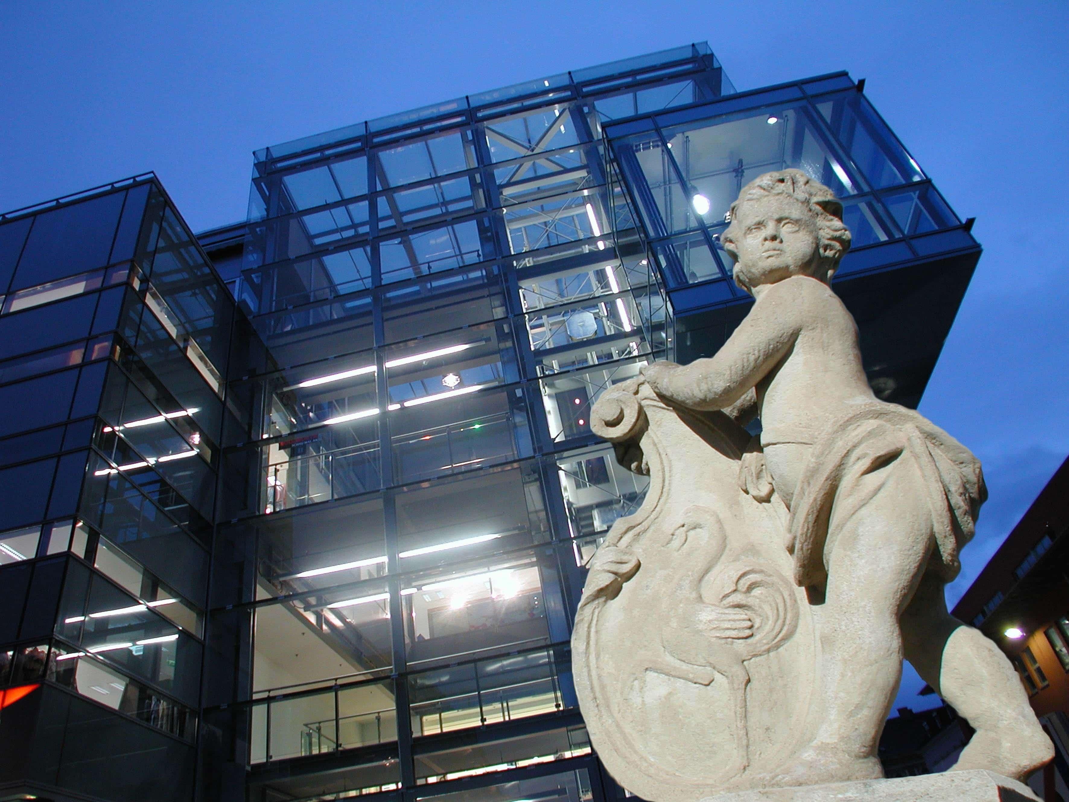 Sie sehen das Kunsthaus in Leoben mit einer Statue. JUFA Hotels bietet erlebnisreichen Städtetrip für die ganze Familie und den idealen Platz für Ihr Seminar.