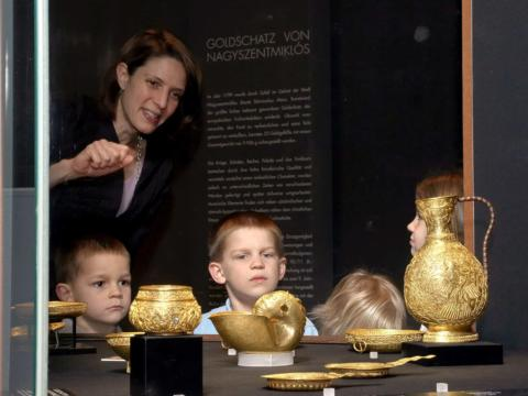 Kinder schauen sich neugierig goldene Ausstellungsstücke im Kunsthistorischen Museum Wien bei einer Führung an. JUFA Hotels bietet erlebnisreichen Städtetrip für die ganze Familie und den idealen Platz für Ihr Seminar.