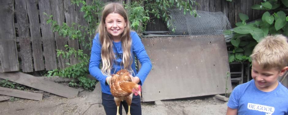 Mädchen hebt eine Henne hoch und freut sich. JUFA Hotels bietet Ihnen den Ort für erlebnisreichen Natururlaub für die ganze Familie.