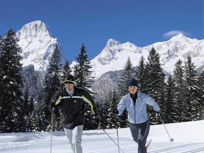 Paar beim Langlaufen auf schöner Langlaufloipe bei Sonnenschein in Pyhrn-Priel. JUFA Hotels bietet erholsamen Familienurlaub und einen unvergesslichen Winterurlaub.