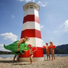 Kinder am Badestrand neben dem Leuchtturm am Stubenbergsee in der Nähe vom JUFA Hotel Stubenbergsee. Der Ort für tollen Sommerurlaub an schönen Seen für die ganze Familie.