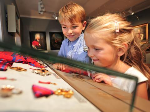 Kinder vor einem Schaukasten im Liechtensteinischen Landesmuseum in der Nähe vom JUFA Hotel Malbun - Alpin-Resort. Der Ort für erholsamen Familienurlaub und einen unvergesslichen Winter- und Wanderurlaub.