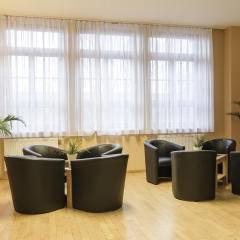 Gemütlicher Lobbybereich mit Sitzgelegenheit im JUFA Hotel Bregenz am Bodensee. Der Ort für tollen Sommerurlaub an schönen Seen für die ganze Familie.