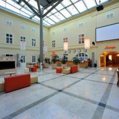 Großzügiger Lobbybereich mit Blick auf große Leinwand im JUFA Hotel Wien City. Der Ort für erlebnisreichen Städtetrip für die ganze Familie und der ideale Platz für Ihr Seminar.